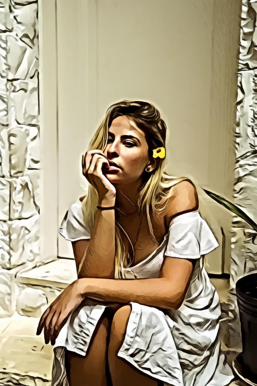 Woman in white dress sitting near closed door