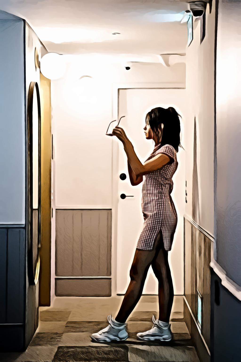 Woman standing in front of mirror holding sunglasses