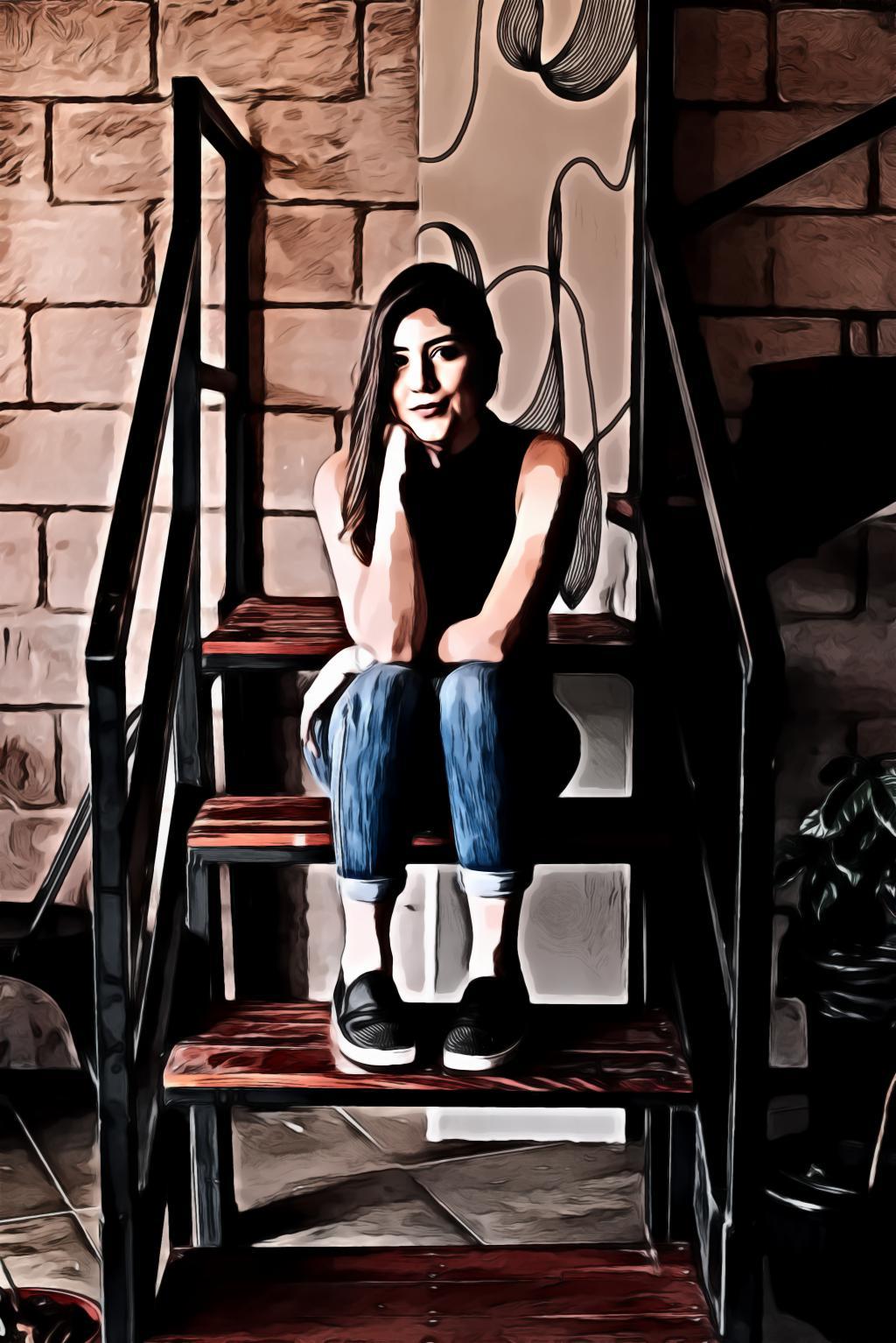 Woman in blue denim jeans sitting on brown stair
