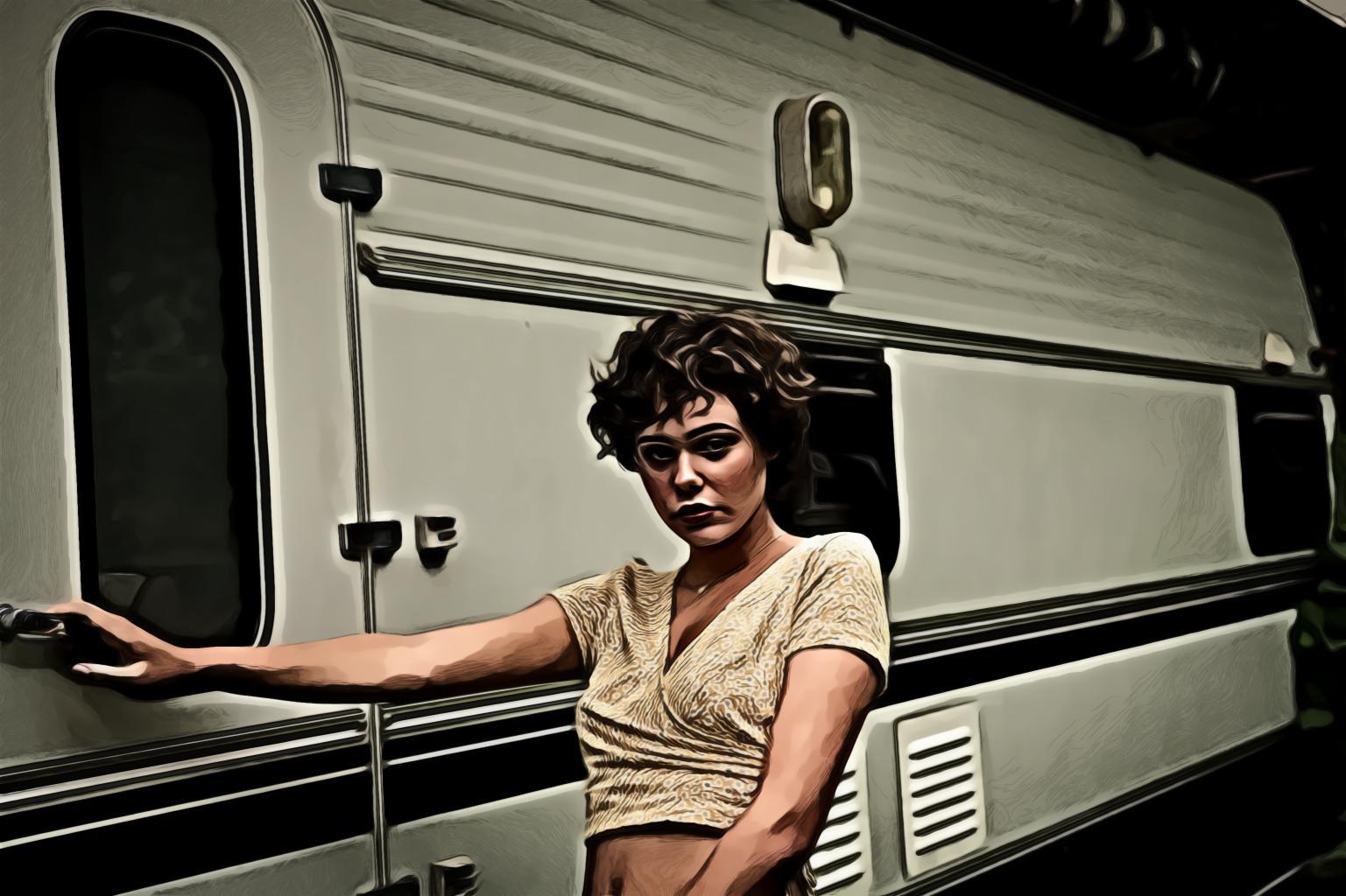 Woman standing beside camper trailer