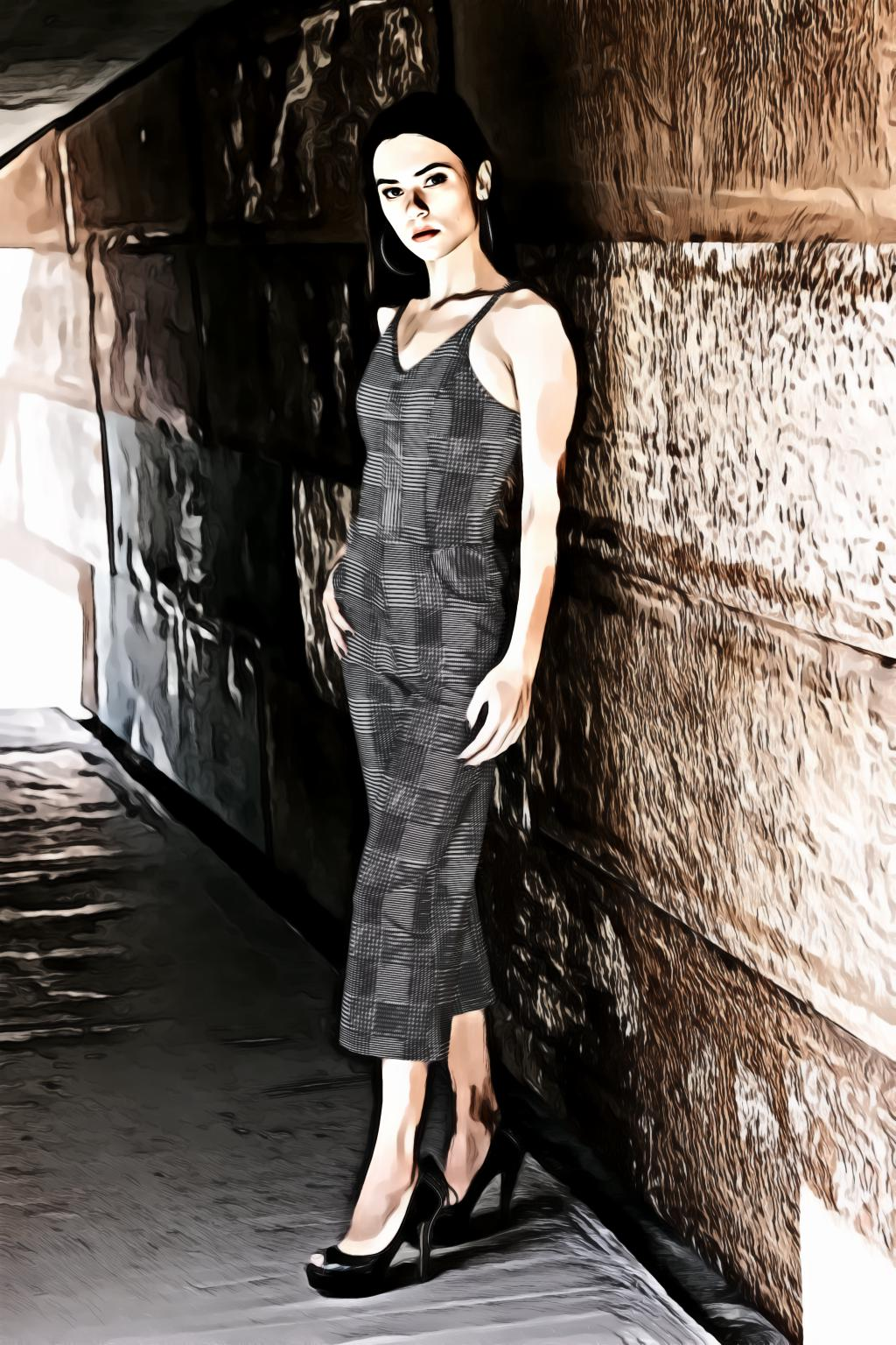 Woman wearing grey sleeveless dress standing near brown wall