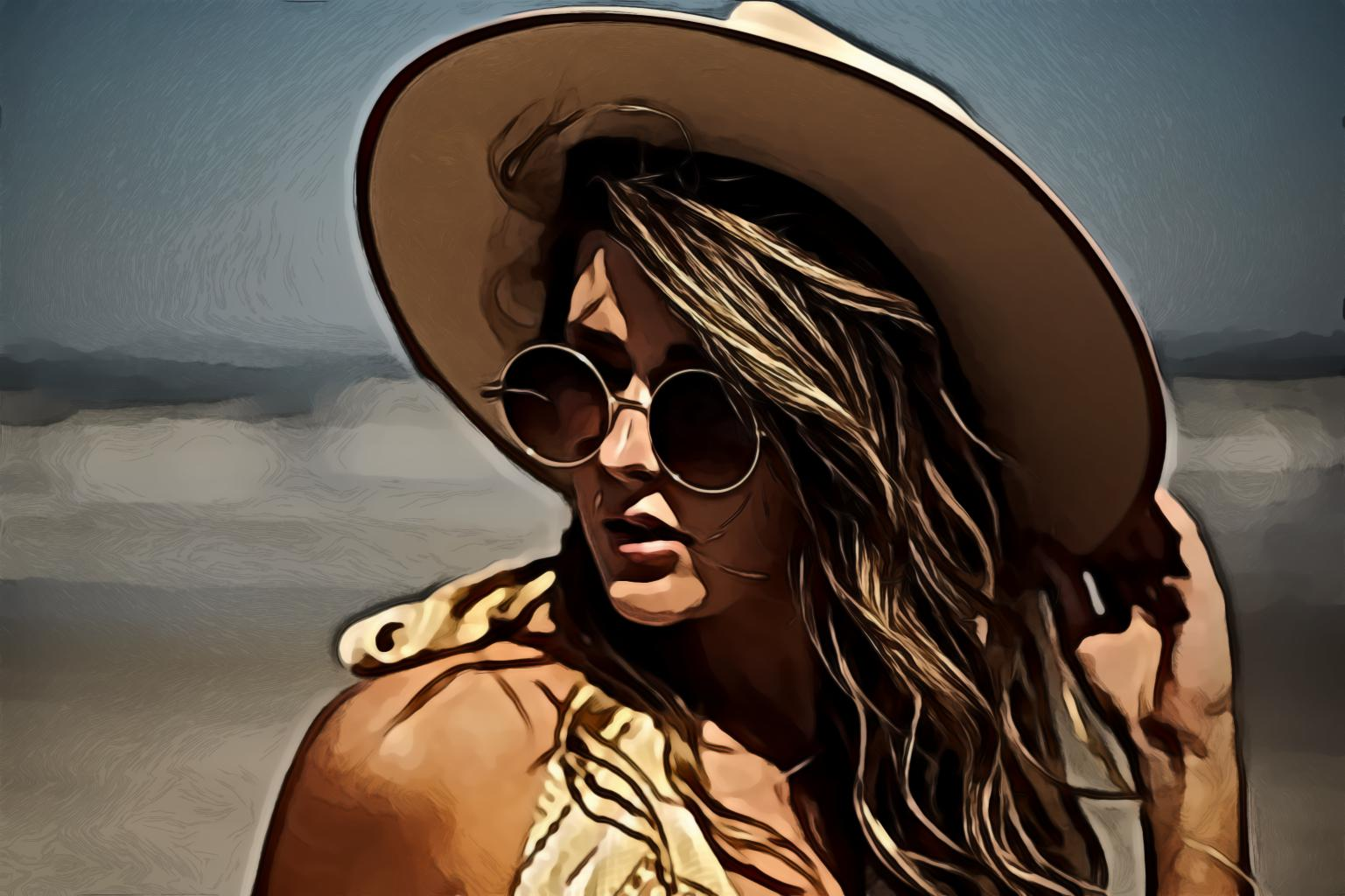 Woman wearing sunhat and sunglasses by the seashore