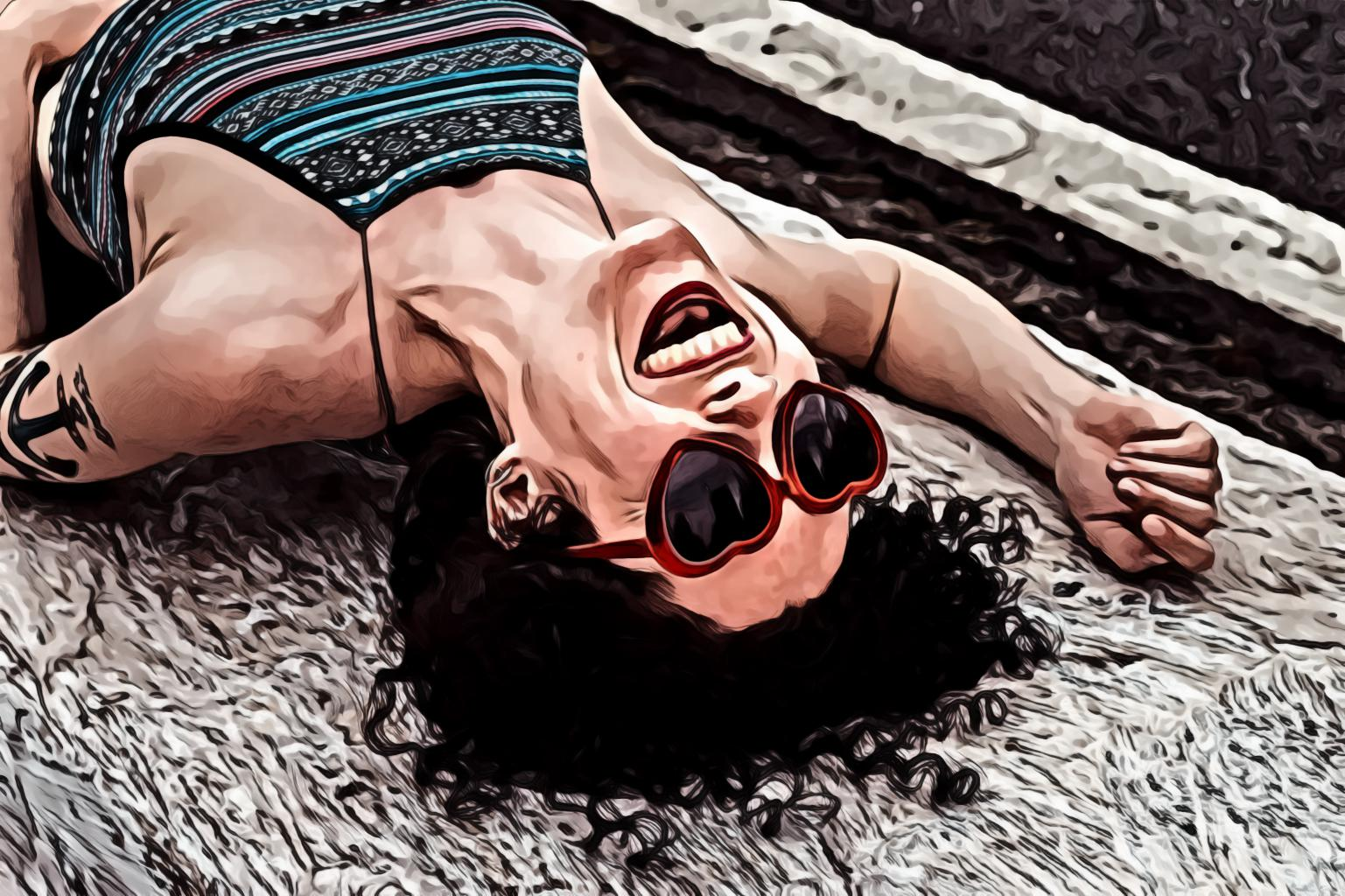 Woman laughing lying on concrete slab
