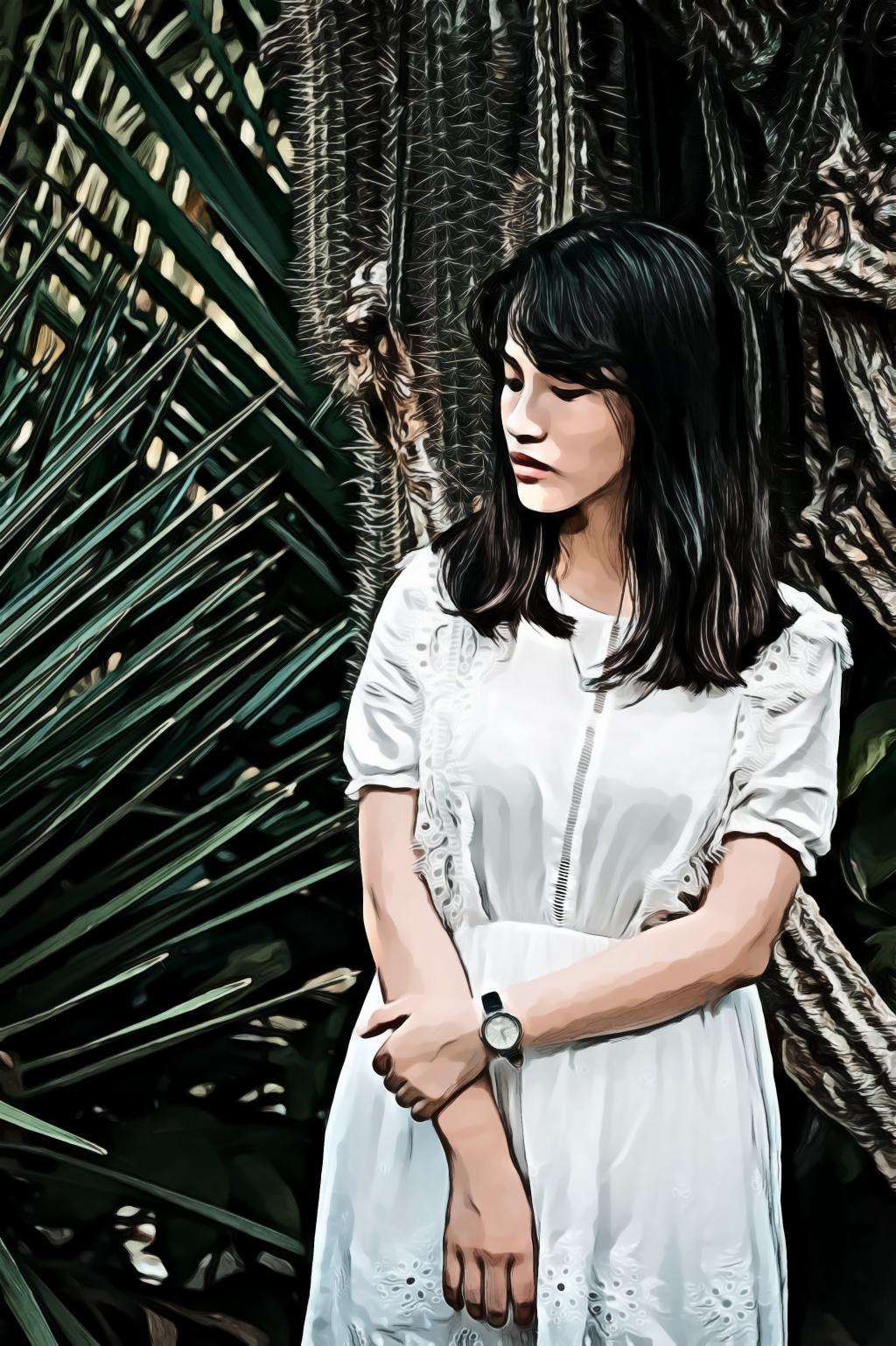 Woman wearing a teal half sleeved dress standing beside green plant