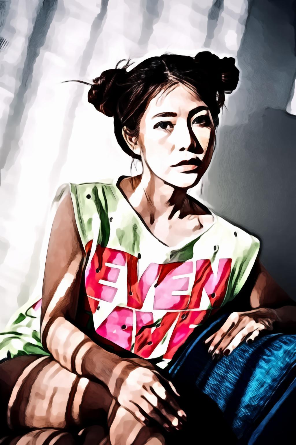 Woman wearing green and pink sleeveless mini dress sitting on blue sofa