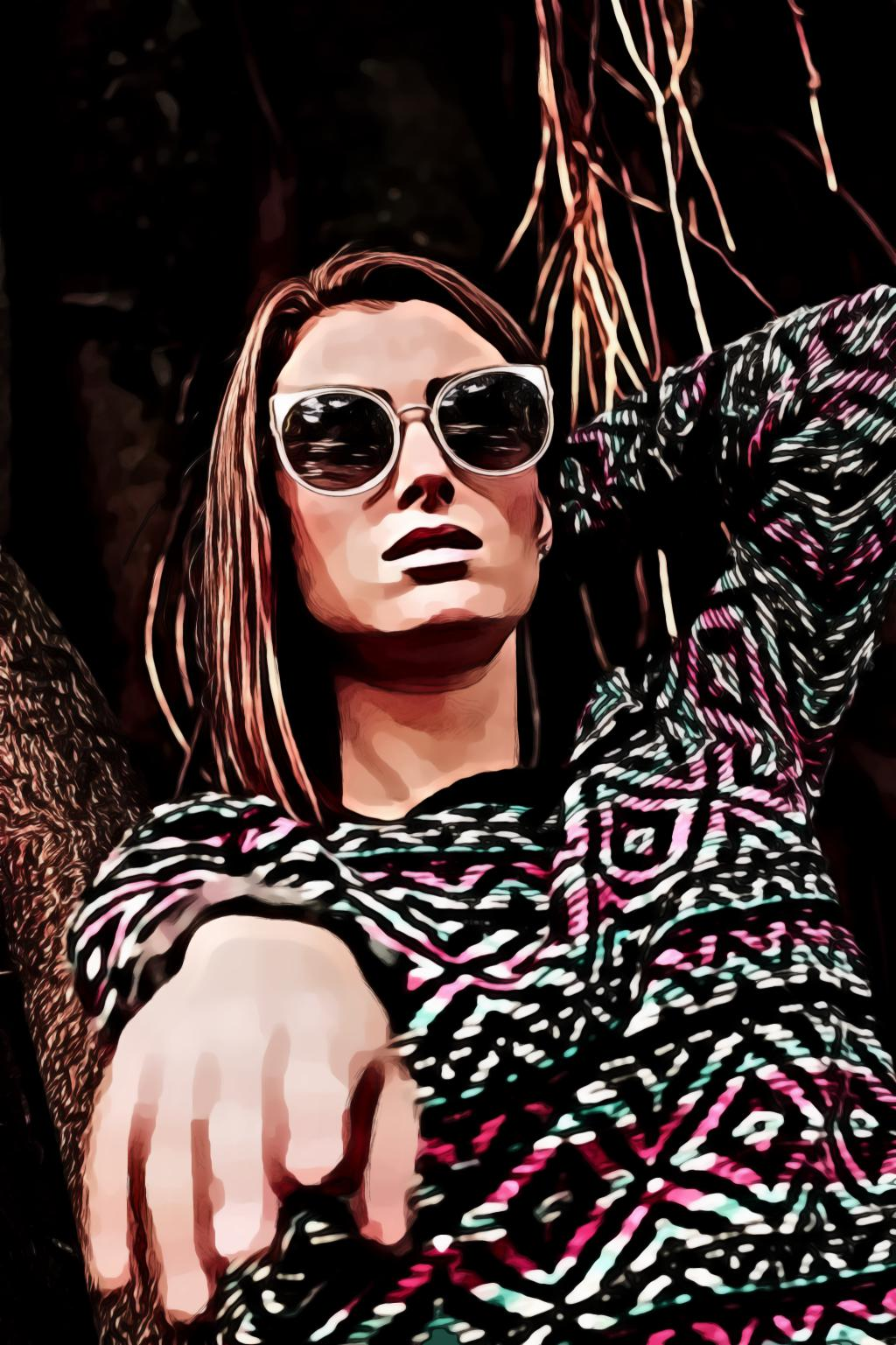 Woman wearing multicolored tribal sweater and sunglasses standing and about to raise her right hand